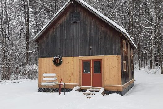 A renovated farm in the snow, with a Christmas wreath